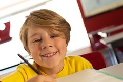 Happy boy looking at camera while drawing sketch on book at desk in a classroom. Front view of happy Caucasian boy looking at camera while drawing sketch on book royalty free stock photos