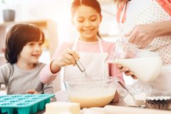 Happy boy looks at little girl who is beating eggs in bowl, where beautiful grandmother pours milk from jug. royalty free stock photos