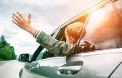 Happy boy looks out from auto window and greets somebody Royalty Free Stock Images