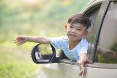 Happy boy looks out from auto window and greets somebody, Happy kids travel by the car stock images