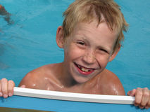 The happy boy looks out of the pool. Stock Photo