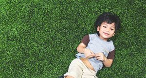Happy boy is lying on artifact grass field. Top view Stock Images