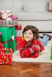 Happy Boy Lying Besides Stacked Christmas Gifts Royalty Free Stock Photo