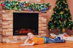 Happy boy lying on the floor near the fireplace Royalty Free Stock Photos
