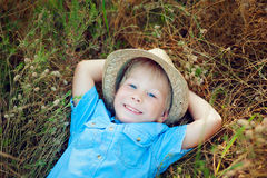 Happy boy lying on the grass. Happy сhild in spring field royalty free stock photos