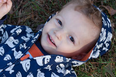 Happy boy. Lying on ground in hooded sweatshirt Royalty Free Stock Photos
