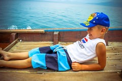 Happy boy lying on sailing boat out at sea Royalty Free Stock Photos