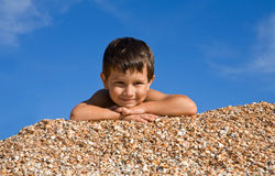 Happy boy lying on shells Stock Photos