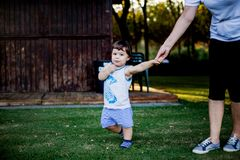 Happy boy making funny faces and expressions while walking with his grandmother. On playground close to small forest with sun behind going through trees and royalty free stock image