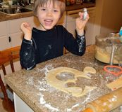 Happy boy making heart cookies royalty free stock photo