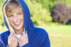 Happy Boy Male Child Teenager Laughing Wearing Hoody. Young happy laughing male boy teenager blond child outside in summer sunshine wearing a blue hoody Stock Photos