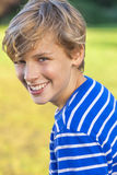 Happy Boy Male Child Teenager Laughing. Young happy laughing male boy teenager blond child outside in summer sunshine wearing a blue striped t-shirt Royalty Free Stock Photo