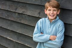 Happy Boy Male Child. Young happy laughing male boy blond child outside leaning against a wall outside arms folded and laughing Stock Photo
