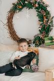 Happy boy with mather near Christmas tree. With feeding black vietnamese piglet. Concept of the Chinese New Year 2019 of the Pig royalty free stock photos