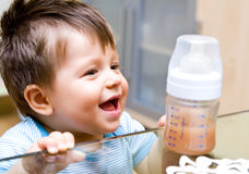 Happy boy with meal. Happy baby boy smiling before a meal from his plastic bottle Royalty Free Stock Images