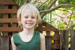 Happy boy messy and grubby from outdoor play. Portrait of a happy boy in backyard with messy hair and face after playing outdoors royalty free stock photography