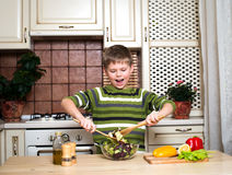 Happy boy mixing a vegetable salad in the kitchen. Stock Images