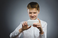 Happy boy with mobile or cell phone making selfie on gray background Stock Image