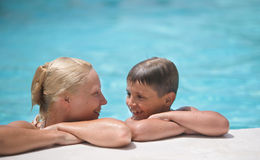 Happy boy and mom in swimming pool Stock Photo