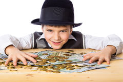Happy boy with money on the table Royalty Free Stock Images
