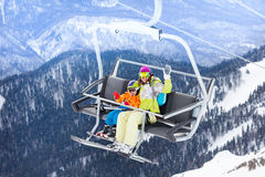 Happy boy with mother sit on skilift ropeway chair Royalty Free Stock Images