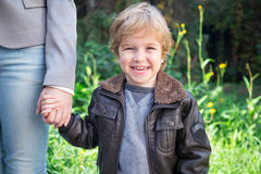 Happy boy in nature holding mother's hand. Royalty Free Stock Photography