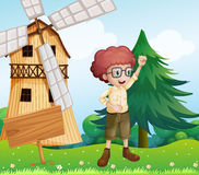 A happy boy near the wooden signboard and the windmill Stock Photography