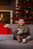 Happy boy opening christmas presents. Portrait of happy little boy sitting on couch opening christmas presents, smiling Royalty Free Stock Image