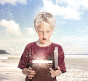 Happy Boy Opening a Gift Box. Happy Young Blonde Boy Opening a Gift Box on the Beach Stock Images
