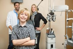 Happy Boy With Optometrists At Store. Portrait of happy boy with optometrists standing in background at store Royalty Free Stock Images