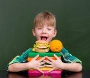 Happy boy with orange and hamburger Stock Images