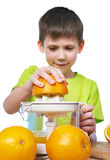 Happy boy with oranges makes juice in juicer isolated Royalty Free Stock Image