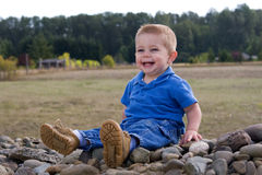 Happy boy outdoors. Happy preschool playing on pile of rocks outdoors Royalty Free Stock Photography