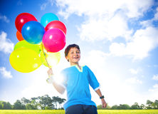 Happy Boy Outdoors With A Dozen Of Helium Balloons Royalty Free Stock Photos
