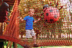 Happy boy overcomes obstacles in rope adventure park. Summer holidays concept. Cute kid playing at rope adventure park. Amusement. Park for kids royalty free stock images
