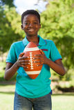 Happy boy in the park with american football Royalty Free Stock Images