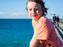 Happy boy on a pier at baltic sea stock photography
