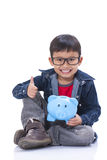 Happy boy with piggy bank and showing thumb up Royalty Free Stock Photo