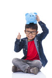 Happy boy with piggy bank and showing thumb up Royalty Free Stock Photos