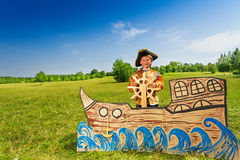 Happy boy in pirate costume holds helm of  ship Royalty Free Stock Photography