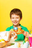 Happy boy with plate, Eastern eggs and rabbit Stock Photos