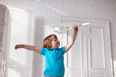 Happy boy play with airplane in hand, child dreams about traveli Royalty Free Stock Image