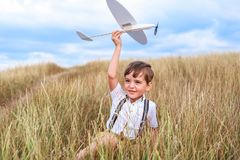 Happy boy play with little white plane. stock photos