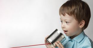 Happy boy play in the tin can phone, boy attached a telephone to. His ear royalty free stock photography