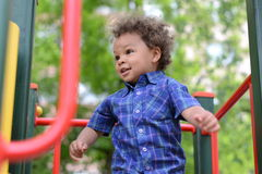 Happy boy on playground. Neatly dressed happy biracial boy busy playing on playground outdoors Stock Photo