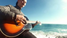 Happy boy playing acoustic guitar at beach. Young musician plays guitar. Teenage guitarist with musical instrument. Boy stock footage