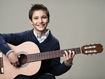 Happy boy playing on acoustic guitar. Stock Image