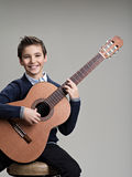 Happy boy playing on acoustic guitar. Royalty Free Stock Image