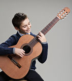 Happy boy playing on acoustic guitar. Royalty Free Stock Photos