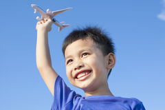 Happy boy playing a airplane toy with blue sky. Background Stock Image